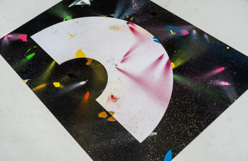 A art print inspired by the coronavirus experience. A black background with a white crescent rainbow shape in the centre. Splattered randomly with different coloured spray paints such as blues, reds, pinks, yellows and greens. Designed and created by artist and designer Liam Hopkins of design studio Lazerian. An angled view of the print. Only 20 made as part of a limited edition set.