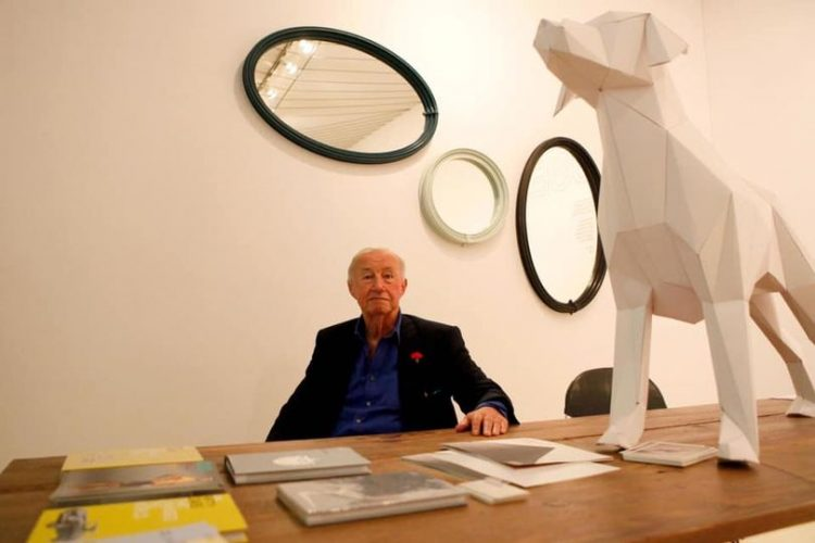 Sir Terence Conran sat at a desk with a huge paper 3D lifesize model of a paper dog.