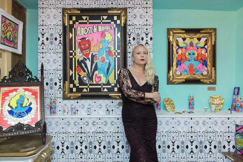 A photograph of a slim blonde lady with red lipstick in a black lace dress. the lady is Grande Dame, an artist and she is surrounded by her work which can be described as psychedelic cartoon. The image is to show the woman behind the artwork. Part of Lazerians Gerald artist spotlight.