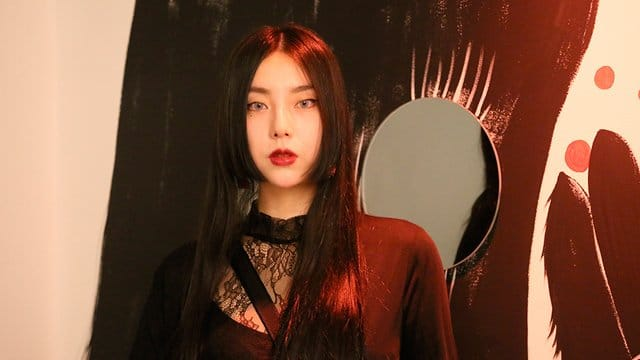 A portrait of a young Korean lady with bright red lips and long straight black hair. It is a portrait of Jang Koal- a female Korean artist. There is a mirror in the background.